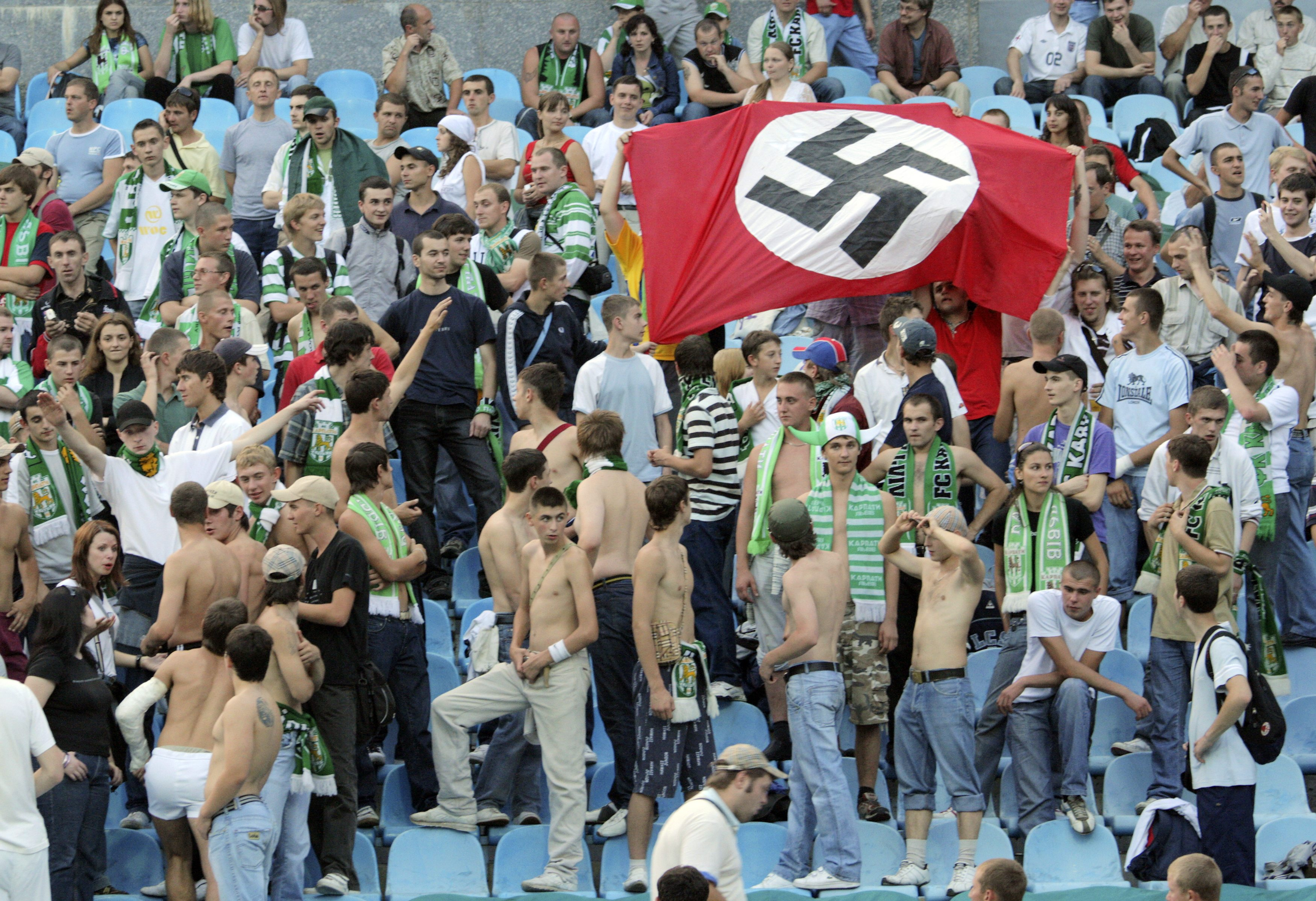 Supporters of Karpaty Lviv hold a German Nazi flag with a swastika as they attend a soccer match against Dynamo Kiev in Kiev August 19, 2007. Poland and Ukraine denounced British press allegations of racism and mob violence at soccer stadiums and assured foreign footballers and fans on May 29, 2012 that they would be safe during the Euro 2012 tournament they will jointly host in June 2012. A BBC Panorama investigative programme on soccer violence filmed in their countries, which aired on May 28, 2012 contained footage of fans giving Nazi salutes, taunting black players with monkey noises, anti-Semitic chants and a group of Asian students being attacked at the Metalist Stadium in Kharkiv, one of the four Ukrainian cities which will be hosting matches. Picture taken August 19, 2007. REUTERS/Stringer/Files (UKRAINE - Tags: SPORT SOCCER CRIME LAW CIVIL UNREST) Picture Supplied by Action Images