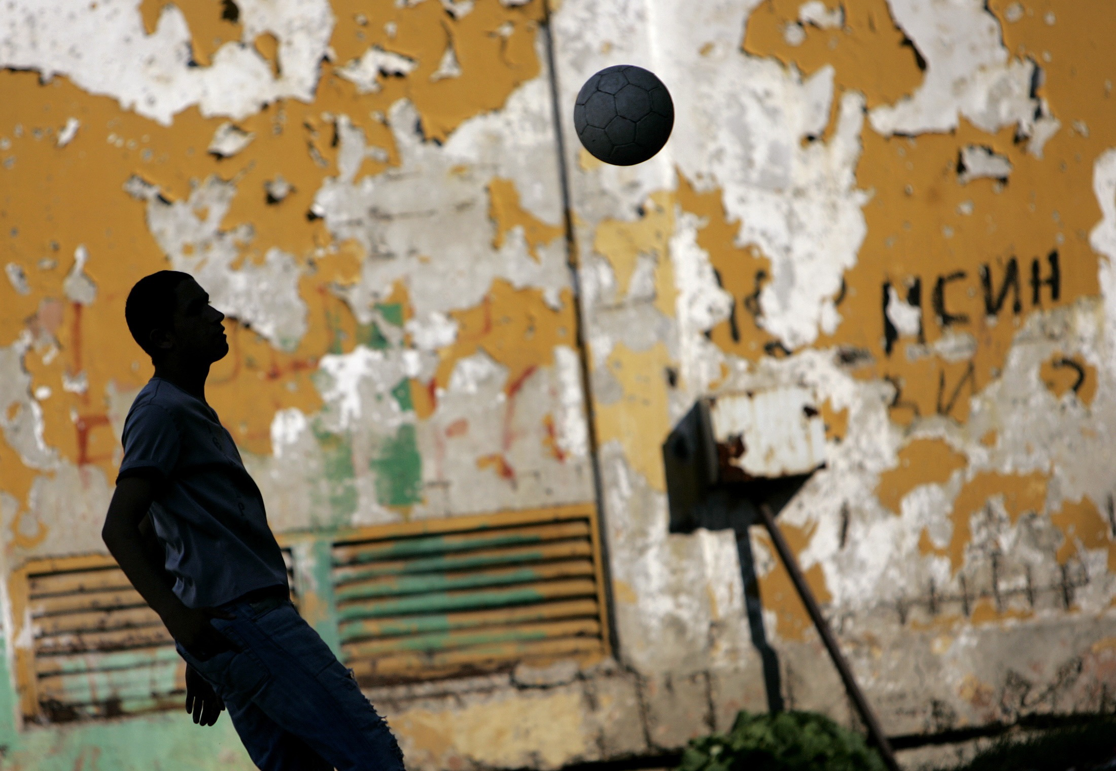 """A Bulgarian Roma boy plays soccer at a school in the Roma suburb of Fakulteta in Sofia, before the visit of U.S. billionaire investor George Soros, June 11, 2007. Soros is in Bulgaria to take part in an international initiative """"Decade of Roma Inclusion"""". Eight south eastern European states launched a 10-year initiative in 2005 to help millions of Roma Gypsies escape the discrimination, segregation and poverty that has isolated them on the margins of mainstream society. REUTERS/Stoyan Nenov (BULGARIA) Picture Supplied by Action Images *** Local Caption *** 2007-06-11T171139Z_01_SOF19_RTRIDSP_3_BULGARIA-SOROS.jpg"""