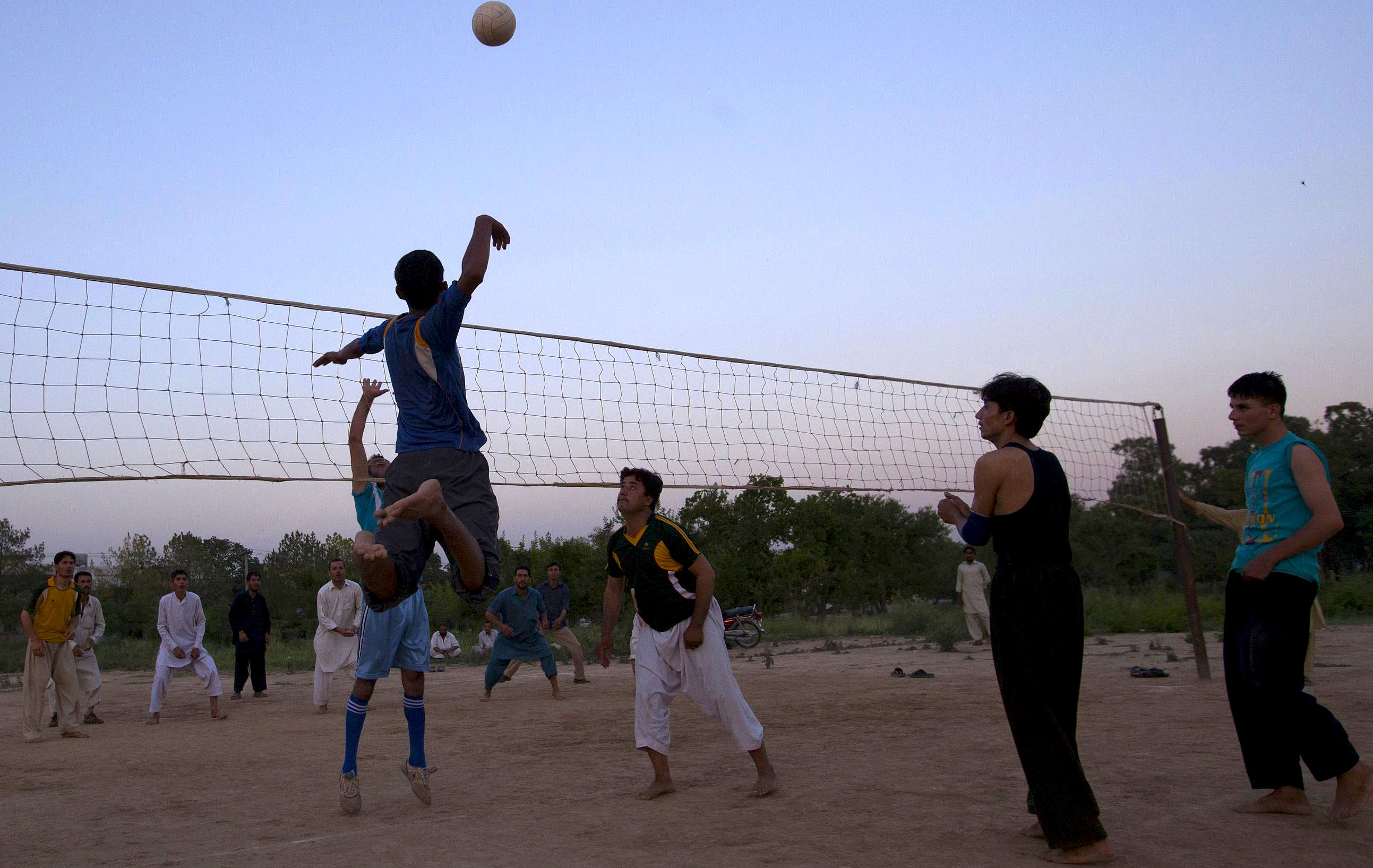 Afghan refugees play volleyball at an open field on the outskirts of Islamabad June 20, 2013. REUTERS/Mian Khursheed (PAKISTAN - Tags: SOCIETY SPORT VOLLEYBALL POLITICS) Picture Supplied by Action Images