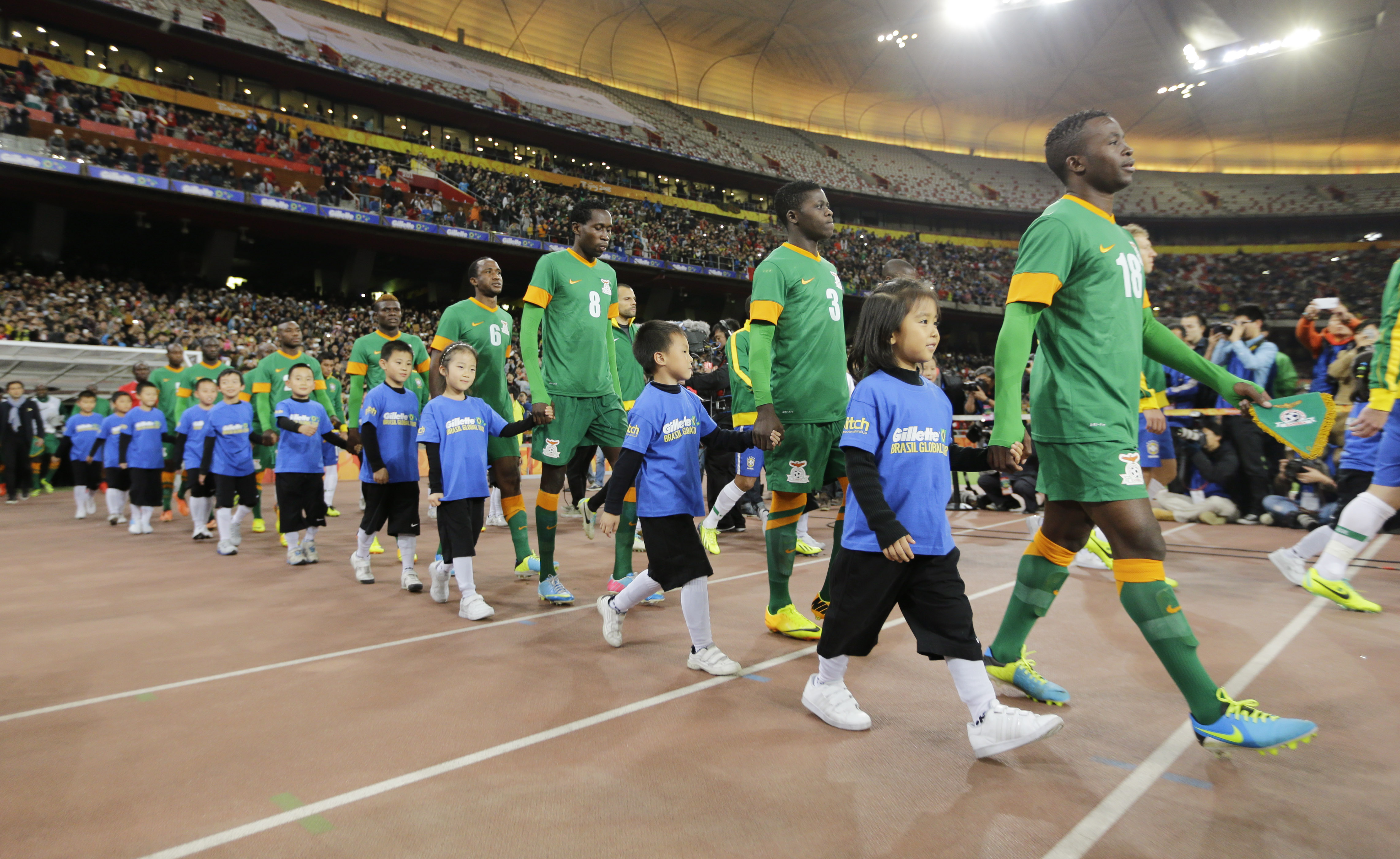 Football - Brazil v Zambia - International Friendly - Beijing National Stadium, Beijing - 15/10/13 Zambia players walk out with mascots Mandatory Credit: Action Images / Liu Yang EDITORIAL USE ONLY.